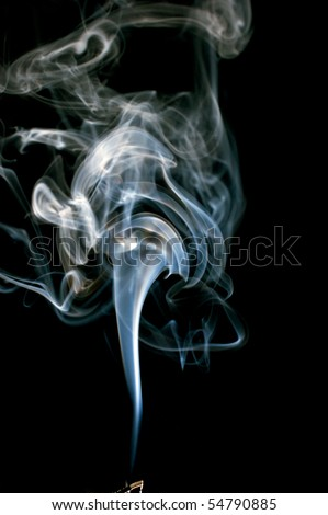 Cloud of real smoke billowing up from a burning incense stick, isolated on black with tip of stick showing at extreme bottom of image. - stock photo