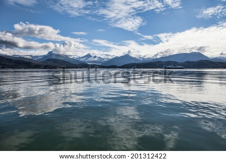 Cloud reflections in calm water in Southeast Alaska near Juneau in summer with a ferry going by in the background.