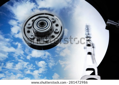 Cloud storage or cloud drive concept image. Hard disk (HDD or Hard drive) with clouds and sky reflecting on disk. Head and Axis with motion blur. - stock photo