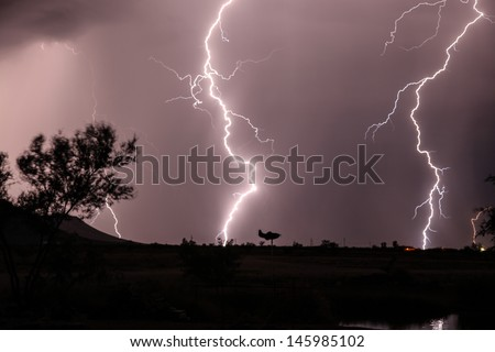 Cloud to ground lightning in Arizona, USA, during summer monsoon season/Weather Vane Silhouette during Nighttime Lightning Strikes in Summer Monsoon Season/Thunderstorm lightning strikes in desert  - stock photo