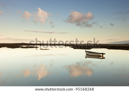 Clouds and a small boat reflected in the water on the marshes at Burnham Deepdale - stock photo