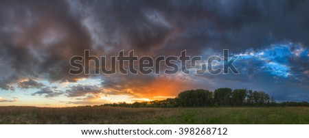 Clouds and colored sunset. The dark clouds before the storm. Beautiful color spots, yellow sun and blue sky. Large high resolution panorama merges from 7 vertical photos. - stock photo