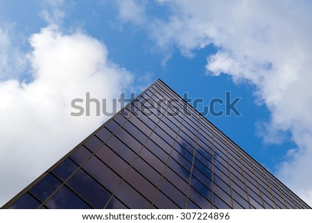clouds and sky are reflected in the mirrored window constructed in high-tech style building - stock photo