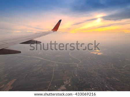 Clouds and sky as seen through window of an aircraft. Looking through window aircraft during flight in wing with a nice blue/purple/orange sky. - stock photo