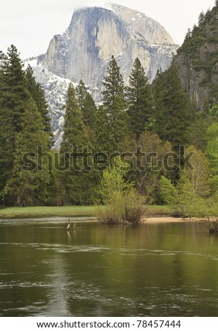 Clouds and snow shroud famous peak of Halfdome in the background as the lazy Merced River reflects the greenery of Yosemite Valley. - stock photo