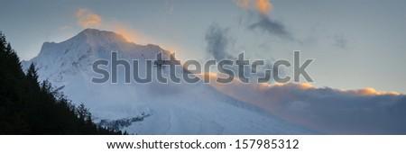 Clouds around Mt. hood lit by sunrise, Oregon - stock photo
