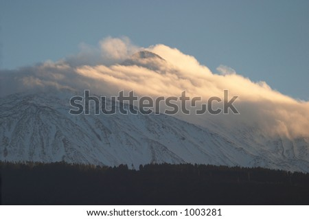Clouds at Teide Volcano top blown by the wind - stock photo