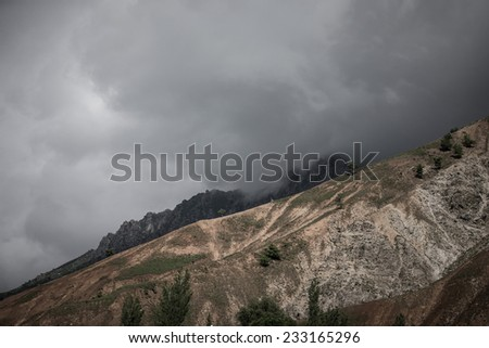 Clouds at the mountains. Stormy wheather. Toned. Dramatic - stock photo