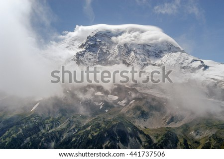 Clouds capping and encircling the peak of Mt. Rainier in Mt. Rainier National Park, Washington State, USA - stock photo