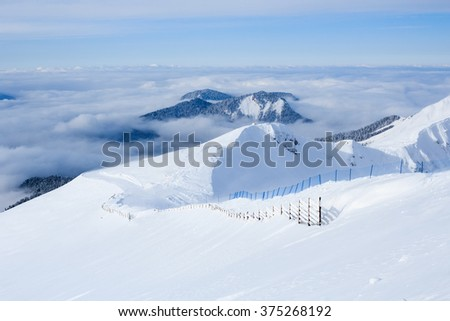 clouds forest and slope with wooden fence of ski trail in the caucasus mountains covered with snow in rosa khutor ski resort sochi - stock photo