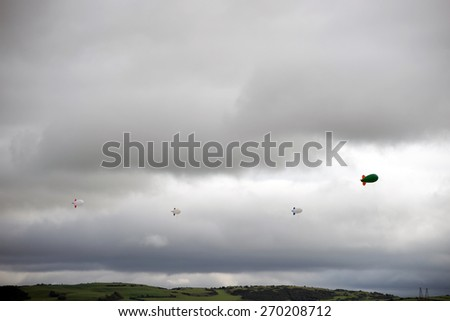 clouds full of air blimps high in the grey sky - stock photo