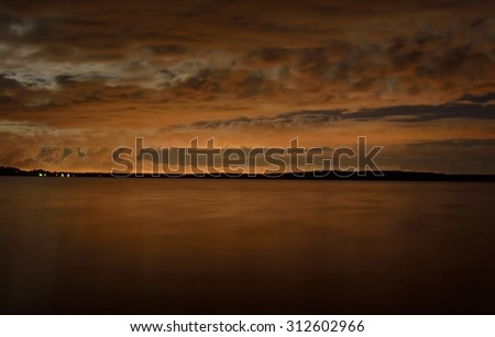 Clouds illuminated by the light on the lake at night. - stock photo