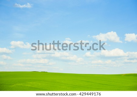 Clouds in a crystal clear, cool-blue sky, an  meadow stretches out across a seemingly endless landscape of gentle hills. The grass is lush and vibrantly colored in several striking shades of green. - stock photo