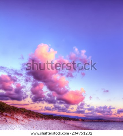clouds over a pink shore at sunset. Processed for hdr tone mapping effect. - stock photo
