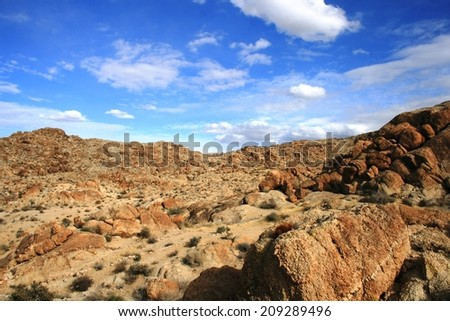 Clouds over red and brown rocks in the desert, California - stock photo