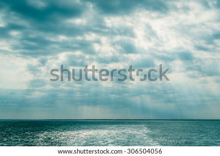 Clouds over the ocean with sunbeams in daylight - stock photo