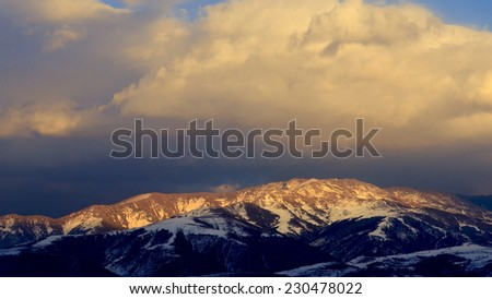 Clouds over the snowy mountains at sunset