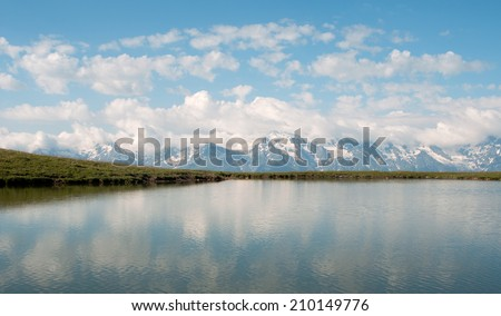 Clouds reflect in the mountain lake. This is Caucasus Mountains - Georgia, Mestia region, Qoruldi lake.