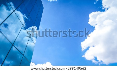 clouds reflected in the many mirrored facets of a modern office building - stock photo