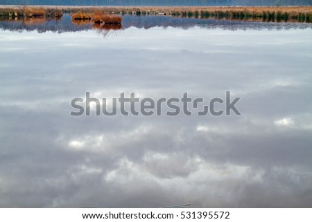 Clouds reflected in the smooth water of a lake on a heath