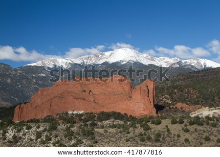 Clouds roll over Pikes Peak in Colorado Springs with the red rock formation of Garden of the Gods
