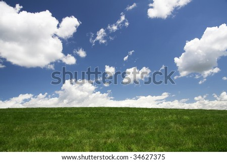Clouds rolling over green pasture - stock photo