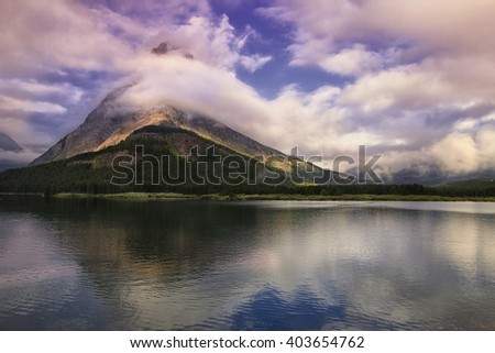 Clouds sweep over Mount Grinnell as it stands over Swiftcurrent Lake in Montana's Glacier National Park