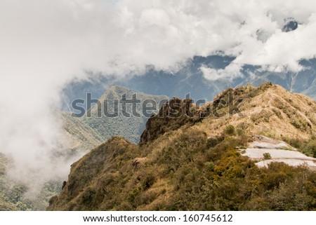 Clouds through the mountains in a valley in Machu Picchu, Cusco, Peru.  - stock photo