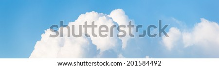 Cloudscape horizontal banner or panorama of beautiful fluffy white cumulus clouds in a sunny blue summer sky