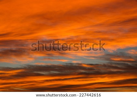 Cloudscape of deep orange and blue layers of color in Autumn sky/Layers of Vivid Orange Color with Narrow Window of Blue across Autumn Sky/Strata of rich orange and blue colors in sky in Fall season - stock photo