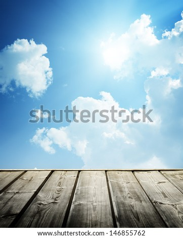 Cloudy blue sky and wood floor - stock photo