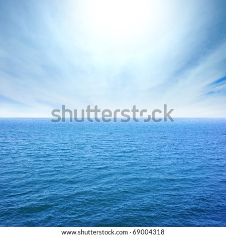 cloudy blue sky leaving for horizon above a blue surface of the sea - stock photo