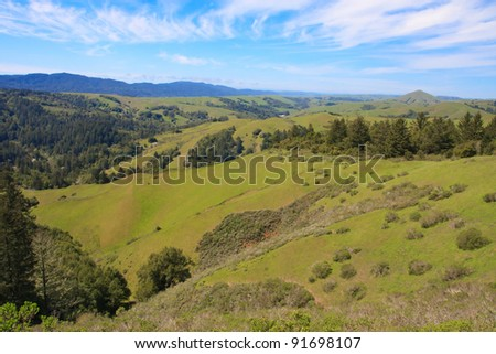 Cloudy blue sky over green hills of Marin County, California - stock photo