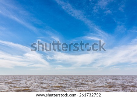Cloudy blue sky. Over river, Buenos Aires. - stock photo