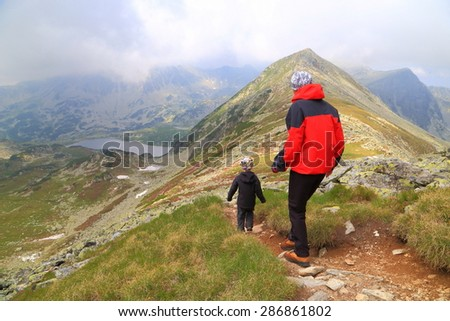 Cloudy day on the mountain with mother and son walking a narrow trail - stock photo