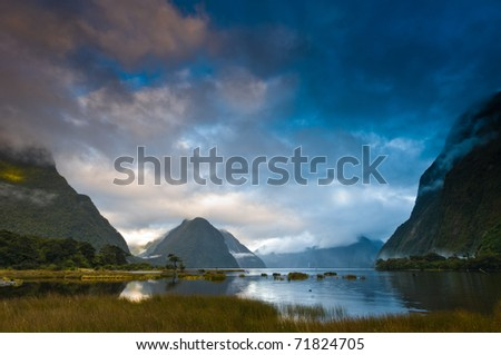 Cloudy morning at milford sound with sunrise in the back ground - stock photo