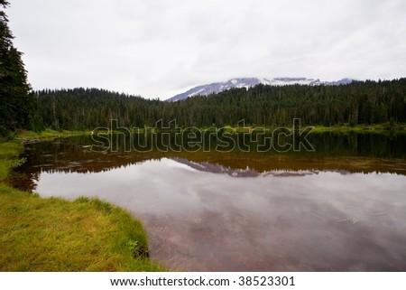 Cloudy Mt. Rainier reflected in Reflection Lake, Mt. Rainier National Park, USA - stock photo