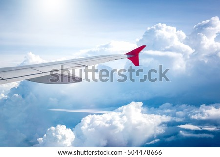 cloudy sky and red airplane wing as seen through window on aircraft.