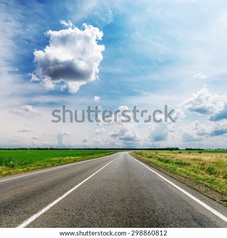 cloudy sky over road in fields - stock photo