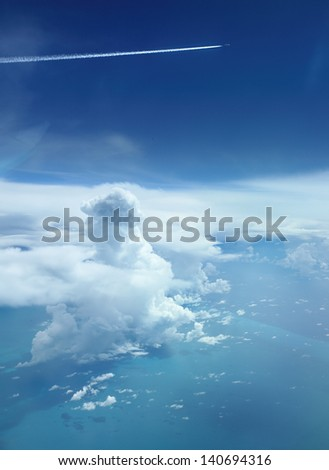Cloudy sky over tropical seas with airplane - stock photo