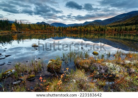 Cloudy sky reflected in Polygonal freshwater lake at dusk in Hibiny mountains above the Arctic Circle, Russia - stock photo