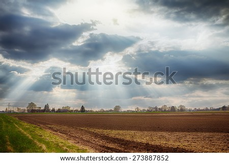 Cloudy sky with sunbeams over arable land in spring - stock photo