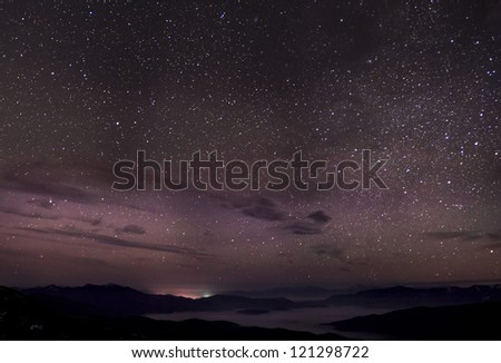 Cloudy star night, fog, mountains and city lights far away. Night panorama of highest Ukrainian peaks. - stock photo
