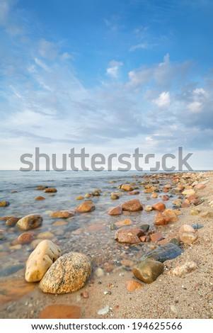 Cloudy summer landscape with coastal stones in the ocean. The Baltic coast, mediterranean sea, Poland. - stock photo