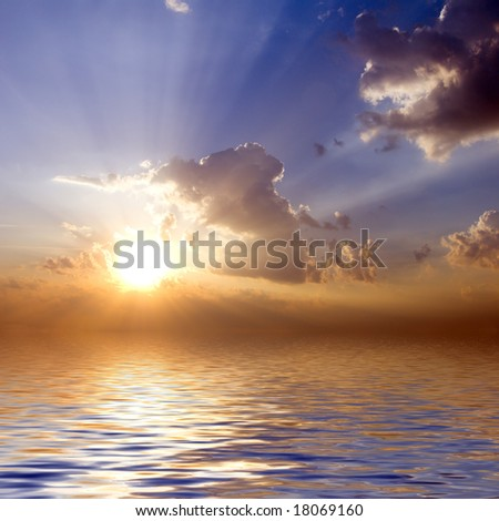 cloudy sunrise with sunbeams blue sky with reflection in water surface - stock photo