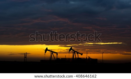 Cloudy Sunset and silhouette of crude oil pumping unit in oil field   - stock photo