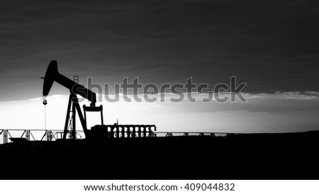 Cloudy sunset and silhouette of crude oil pumping unit in oilfield - black and white