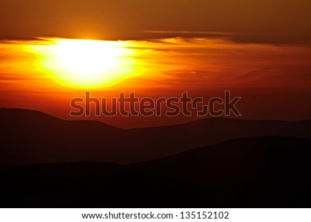 Cloudy sunset in the mountains - stock photo