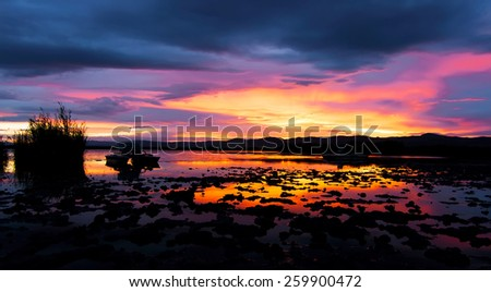 Cloudy sunset next to a lake in the siberian steppe  - stock photo