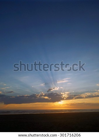 Cloudy Sunset Over the Ocean with Sunbeams in the Sky - stock photo